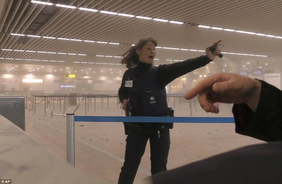 A police officer directs passengers in a smoke filled terminal at Brussels Airport after two explosions ripped through the terminal