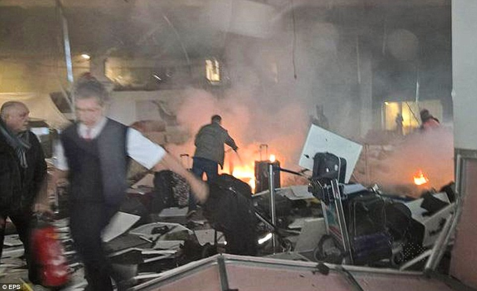 Fires burn among bags and debris as passengers flee the terminal in the immediate aftermath of two explosions at the check-in desks
