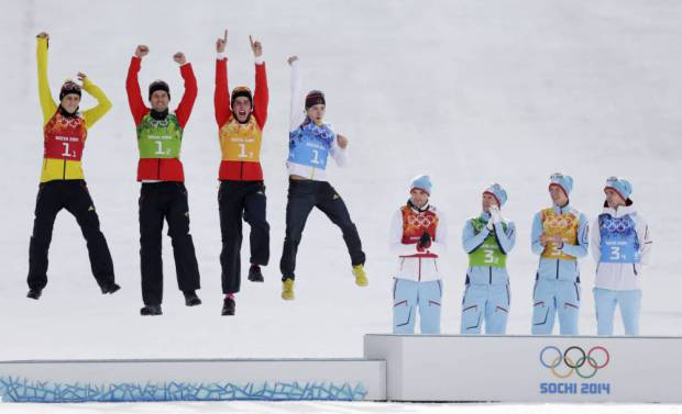 Germany's team Eric Frenzel, Bjoern Kircheisen, Johannes Rydzek and Fabian Riessle, from left, celebrate winning the silver as Norway's gold medal winners Magnus Hovdal Moan, Haavard Klemetsen, Magnus Krog and Joergen Graabak, from left, applaud during the flower ceremony of the Nordic combined Gundersen large hill team competition at the 2014 Winter Olympics, Thursday, Feb. 20, 2014, in Krasnaya Polyana, Russia. (AP Photo/Matthias Schrader)