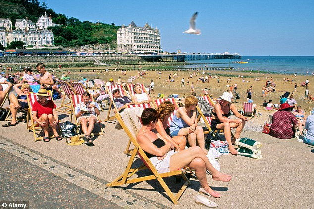 Stay-at-home: Seaside resorts - such as Llandudno, north Wales - are expected to be heaving this weekend