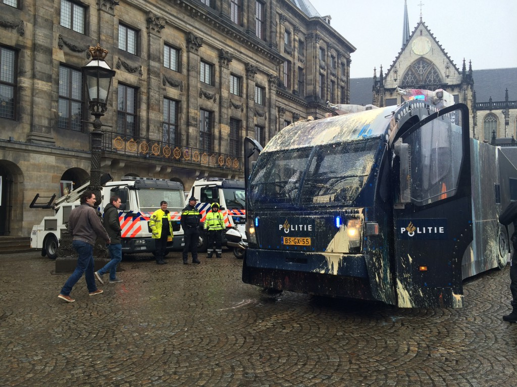 Amused police look on as colleagues return in a paint-bombed water cannon truck. March 25, 2015 (photo: Zack Newmark / NL Times)