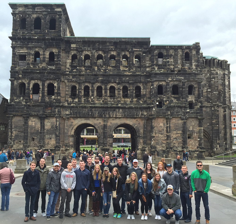 The students are featured in front of the Porta Nigra Gate, one of the original gates from the Roman Empire, in Trier, Germany.
