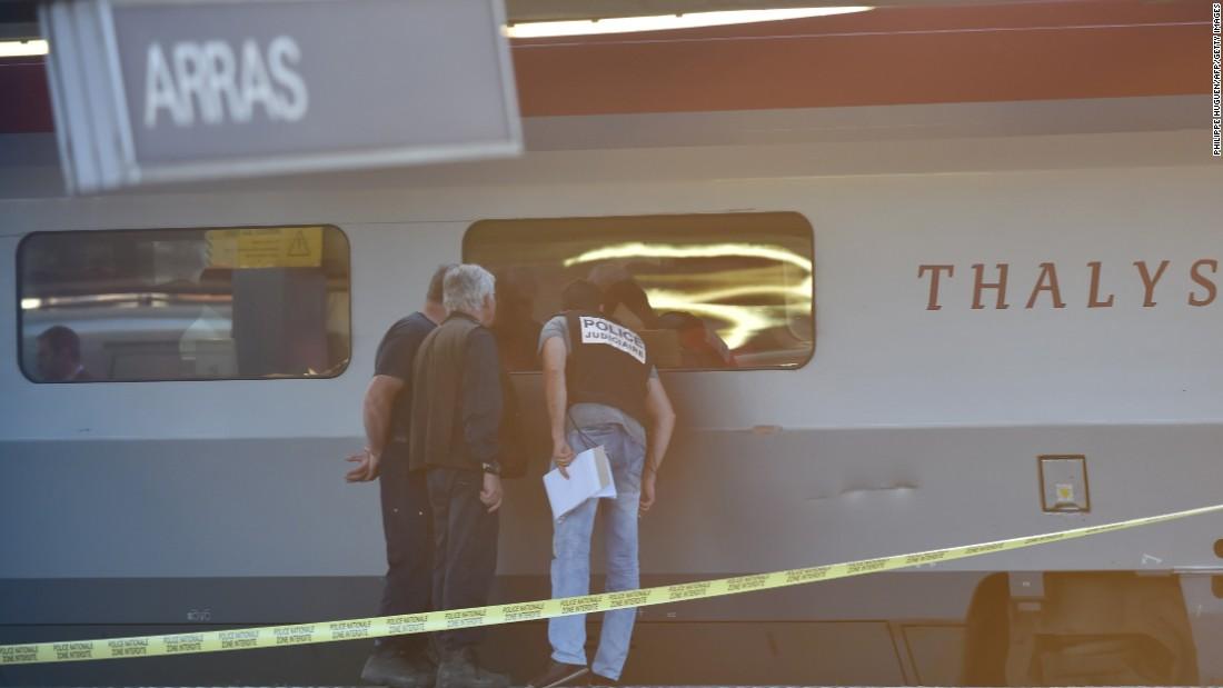 Crime investigators look into the window of the train.