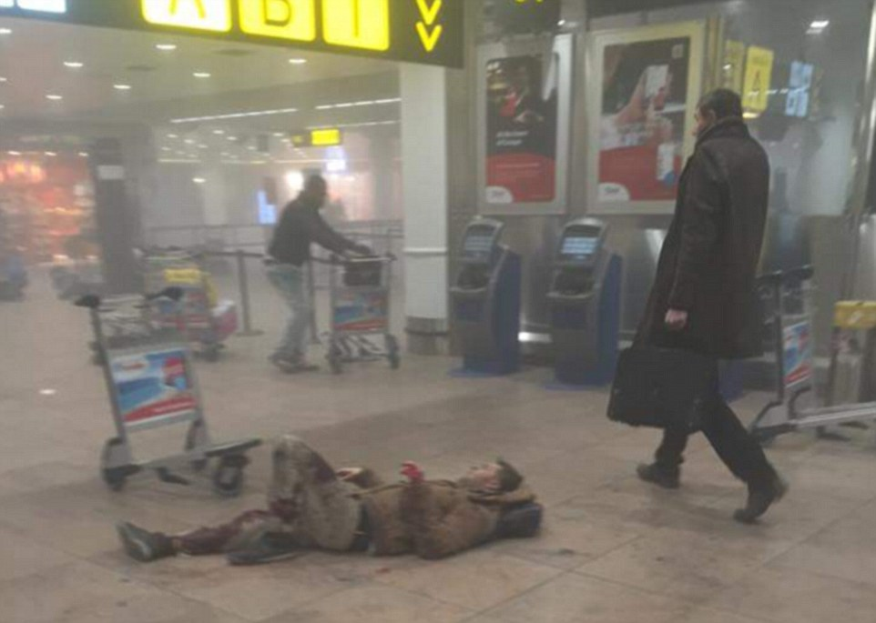 A man lies injured on the floor after two explosions detonated near the American Airlines check-in desk