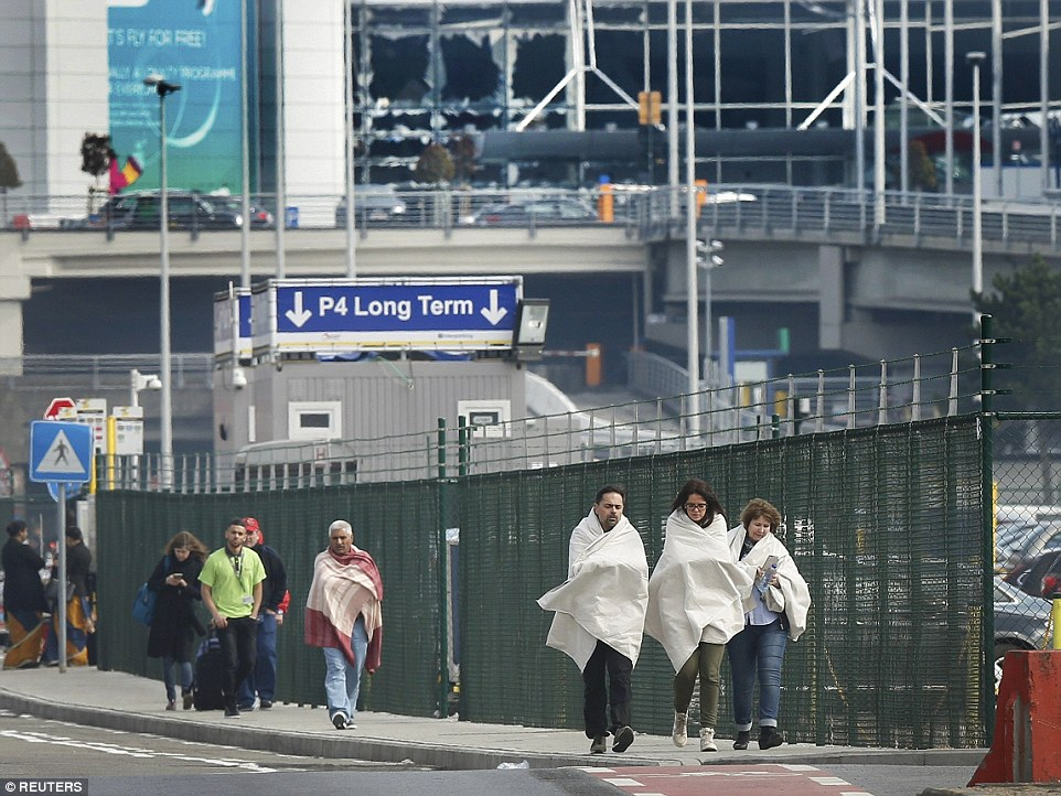 Survivors wrapped in blankets leave the scene of explosions at Brussels-Zaventem airport in the wake of the suicide bomb blasts