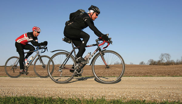 Andrew Folpe, left, and Joachim Mertens ride their bikes on an unpaved road Saturday, May 11, 2013, to train for the Almanzo. The race isn't for just anyone: riders will loop a 100-mile trail, some will ride for 162 miles, and a hearty bunch will pedal for a 380-miles around southeastern Minnesota's gravel roads. Riders will hail from as far as Amsterdam, Los Angeles and Florida for the casual, yet unforgiving bicycling event. (Photo by Alex Kolyer for MPR)