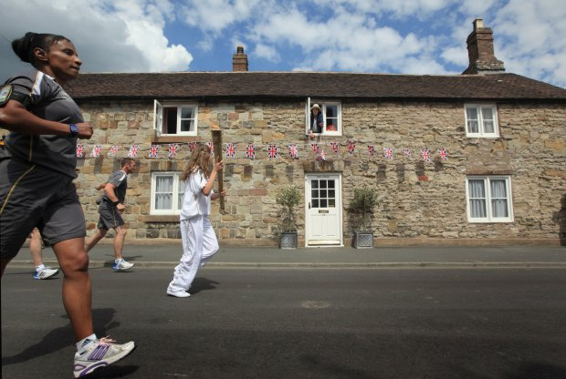 Google doodle: History of the Olympic games and how Britain made it global. MUCH WENLOCK, ENGLAND - MAY 30: Resident Gabrielle Drake looks out of the window of Hollybush Cottage as the Olympic Torch passes through Much Wenlock the birthplace and former home of William Penny Brookes the founding father of the modern Olympics on May 30, 2012 in Much Wenlock, England. The Shropshire town of Much Wenlock is the birthplace of William Penny Brookes the founding father of the modern Olympics. The first Wenlock Olympian games were held in 1850 for 'every grade of man' amongst the athletic events it even included knitting and academic studies such as writing and arithmetic. Wenlock, one of the London 2012 mascots is named in honour of the Shropshire town. (Photo by Christopher Furlong/Getty Images)