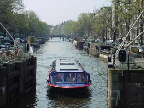 A tourist boat cruises one of the main canals in Amsterdam, a city that is growing in popularity with travelers from the United States. (Doug Walker, RN-T.com)